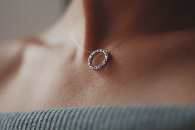 closeup-shot-female-wearing-beautiful-silver-necklace-with-pendant_181624-15490