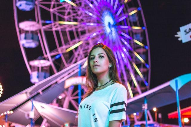 Dievča stojace pred kolotočom s bielym tričkom s nápisom