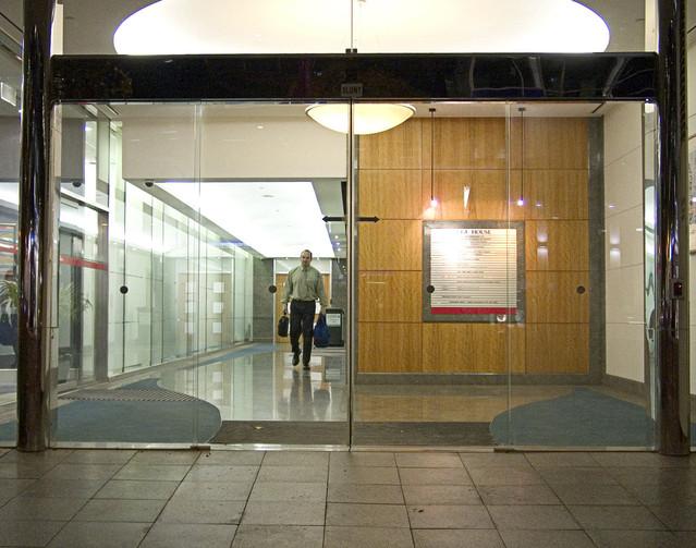 Kancelária, muž kráča s kufrom v ruke, sklenené steny, sklenené dvere