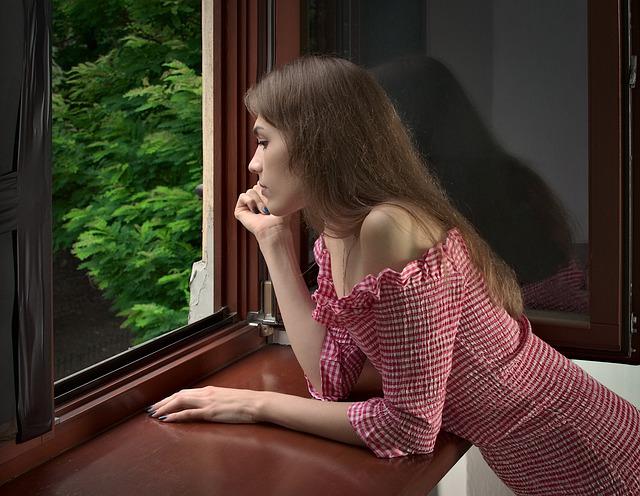 Žena sa pozerá von z okna s drevenými rámami na stromy.jpg