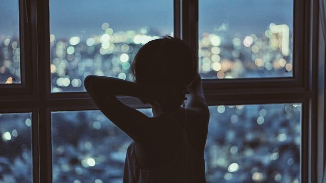 Žena stojí pri veľkom okne a pozerá na nočné mesto.jpg